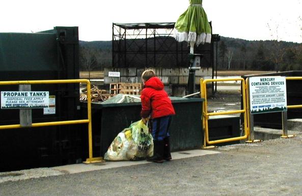 yellow bag being deposited in bin